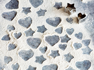 Heart and star shapes patterns in flour with cookie cuttersの写真素材 [FYI03561818]