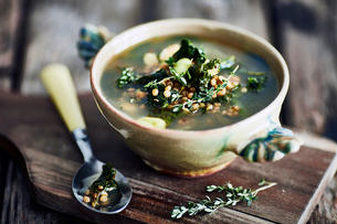 Bowl of broth on wooden cutting boardの写真素材 [FYI03561820]