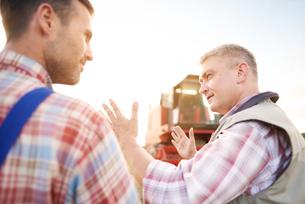 Rear view of farmers in wheat field chattingの写真素材 [FYI03561842]