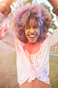 Portrait of young woman at festival, covered in colourful powder paintの写真素材 [FYI03561852]