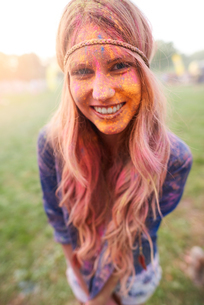 Portrait of young woman at festival, covered in colourful powder paintの写真素材 [FYI03561861]