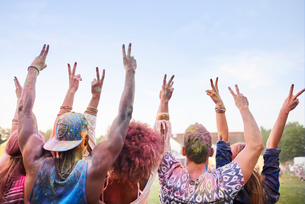Group of friends at festival, covered in colourful powder paint, arms raised, making peace sign withの写真素材 [FYI03561868]
