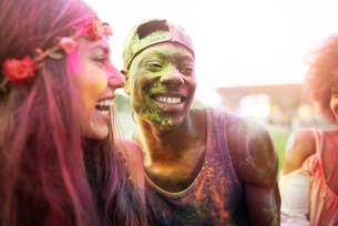 Group of friends at festival, covered in colourful powder paintの写真素材 [FYI03561870]