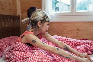 Two women looking through window from log cabin bed, Tyrol, Austriaの写真素材 [FYI03561933]