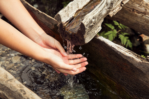 Female hands under fresh running trough water, Sattelbergalm, Tyrol, Austriaの写真素材 [FYI03561954]