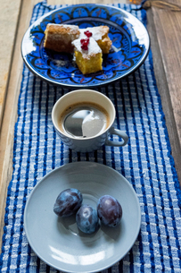 Table with bowl of cake, black coffee and plumsの写真素材 [FYI03562073]