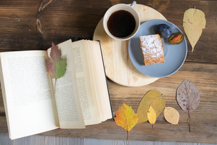 Overhead view of coffee and cake with book and autumn leavesの写真素材 [FYI03562074]