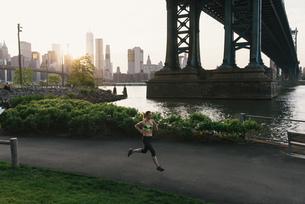 Young woman exercising outdoors, running along pathway underneath Brooklyn Bridge, Brooklyn, New Yorの写真素材 [FYI03562172]