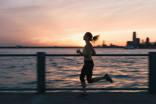 Young woman exercising outdoors, running by waterfront, Brooklyn, New York, USAの写真素材 [FYI03562184]