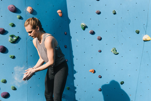 Young woman dusting hands, preparing to use climbing wall, Brooklyn Bridge Park, Brooklyn, New York,の写真素材 [FYI03562192]