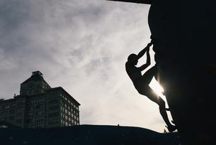 Young woman on climbing wall at sunset, Brooklyn Bridge Park, Brooklyn, New York, USAの写真素材 [FYI03562222]