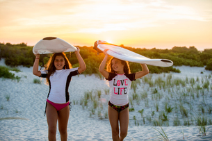 Two young girls on beach, carrying surfboardsの写真素材 [FYI03562256]