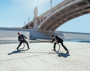 Businessman doing tug of war with rope, Los Angeles river, California, USAの写真素材 [FYI03562448]