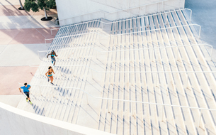 Man and two young women training, running up sport facility stairway, downtown San Diego, Californiaの写真素材 [FYI03562465]