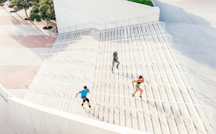 Man and two young women training, moving up sport facility stairway, downtown San Diego, California,の写真素材 [FYI03562466]