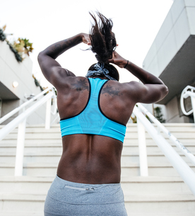 Rear view of woman training, tying ponytail at sport facility, downtown San Diego, California, USAの写真素材 [FYI03562487]