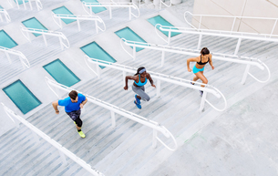 High angle view of man and two women training, running up stairway at sport facility, downtown San Dの写真素材 [FYI03562494]