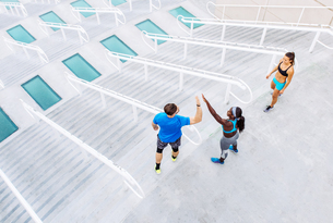 High angle view of man and women training, high fiving on stairway at sport facility, downtown San Dの写真素材 [FYI03562495]