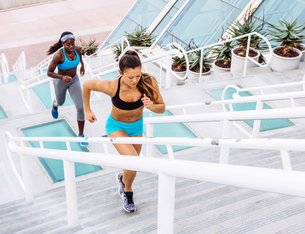Side view of two women training, running up stairway at sport facility, downtown San Diego, Californの写真素材 [FYI03562502]
