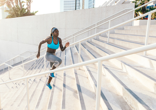 Young woman training, running up sport facility stairway, downtown San Diego, California, USAの写真素材 [FYI03562505]