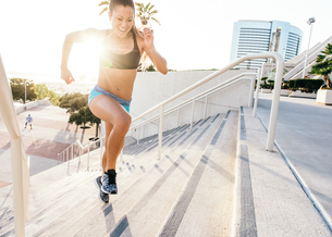 Young woman training, running up stairway at sport facility, downtown San Diego, California, USAの写真素材 [FYI03562507]