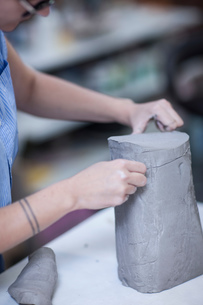 Cropped shot of female potters slicing clay in workshopの写真素材 [FYI03562548]