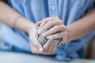 Female potters hands shaping clay in workshopの写真素材 [FYI03562549]