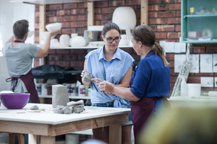 Two female potters shaping clay on workbench in workshopの写真素材 [FYI03562551]