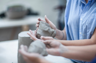 Cropped shot of two female potters shaping clay in workshopの写真素材 [FYI03562552]