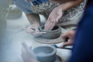 Hands of female potters shaping clay pots in workshopの写真素材 [FYI03562557]
