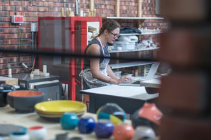 Female potter checking online orders in workshopの写真素材 [FYI03562570]