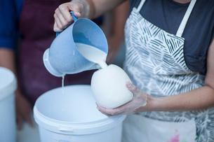 Female potter pouring ceramic glaze into vase in workshopの写真素材 [FYI03562577]