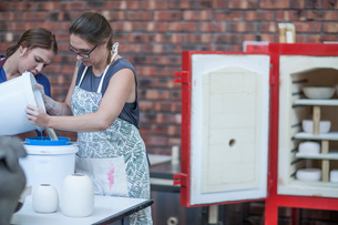 Female potter pouring ceramic glaze into bucket in workshopの写真素材 [FYI03562578]