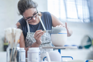 Female potter painting ceramic glaze on vase in workshopの写真素材 [FYI03562579]