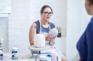 Female potter explaining glaze to trainee in workshopの写真素材 [FYI03562581]