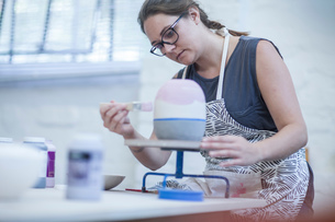 Female potter painting ceramic glaze on vase in workshopの写真素材 [FYI03562582]