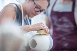 Female potter smoothing surface on vase in workshopの写真素材 [FYI03562583]