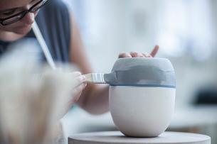Female potter painting ceramic glaze on vase in workshopの写真素材 [FYI03562584]