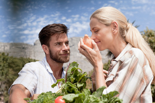 Mature couple in garden, woman smelling onionの写真素材 [FYI03562643]