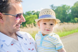 Father holding baby boy wearing straw hatの写真素材 [FYI03562663]