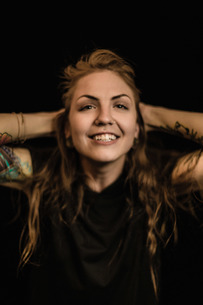 Portrait of woman with tattoo and piercings, hands behind head looking at camera smilingの写真素材 [FYI03562726]