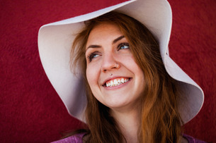 Portrait of pierced woman wearing sunhat looking away smilingの写真素材 [FYI03562730]