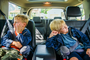 Twin brothers sitting in back of vehicle, bored expressionsの写真素材 [FYI03562847]