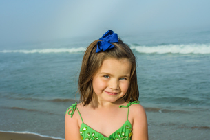 Portrait of cute girl wearing hair ribbon on beach, Asbury Park, New Jersey, USAの写真素材 [FYI03563006]