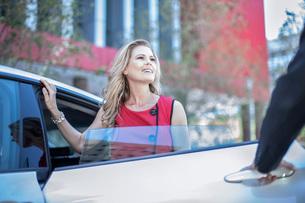 Man opening car door for city businesswomanの写真素材 [FYI03563081]