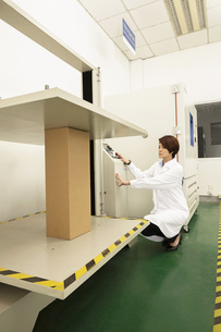 Female technician operating packaging machine in printing and packaging factory, Chinaの写真素材 [FYI03563131]