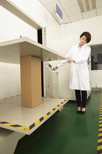 Female technician operating packaging machine in printing and packaging factory, Chinaの写真素材 [FYI03563133]