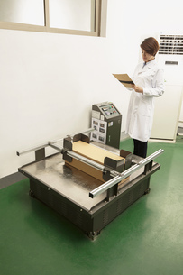 Female technician reading paperwork by packaging machine in printing and packaging factory, Chinaの写真素材 [FYI03563142]