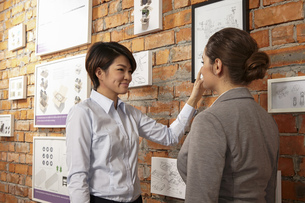 Female asian worker showing caucasian female manager print products on wall of printing and packaginの写真素材 [FYI03563145]