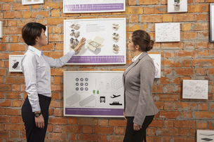 Worker showing framed product to manager on printing and packaging factory wall, Chinaの写真素材 [FYI03563146]